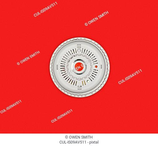 Smoke alarm with red button on red background