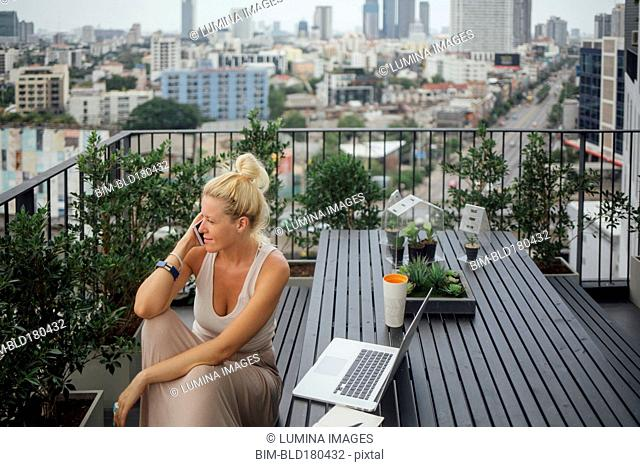 Caucasian woman talking on cell phone on balcony