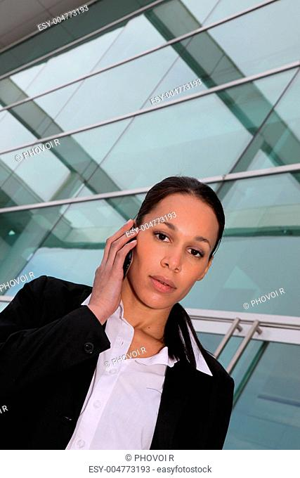 Businesswoman speaking on mobile telephone in glass building