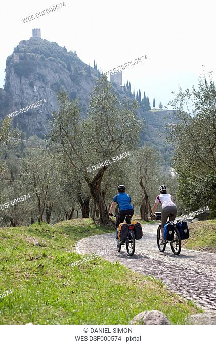 Italy, Trento, Man and woman cycling, Castle of Arco in background