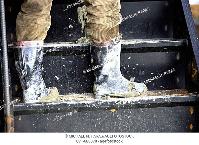 Construction worker boots messed with concrete