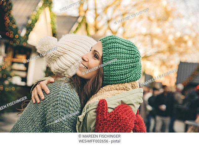 Happy women hugging on the Christmas Market