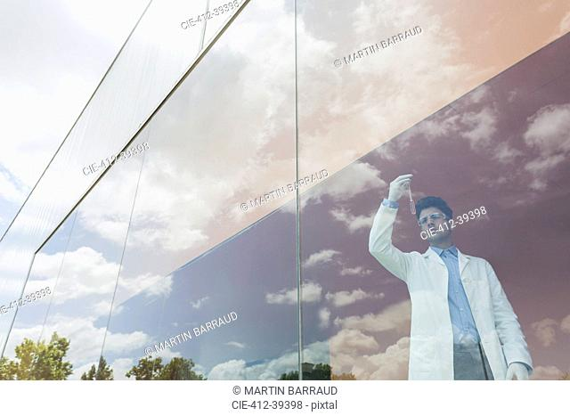 Scientist examining liquid in beaker at modern window with cloud reflections