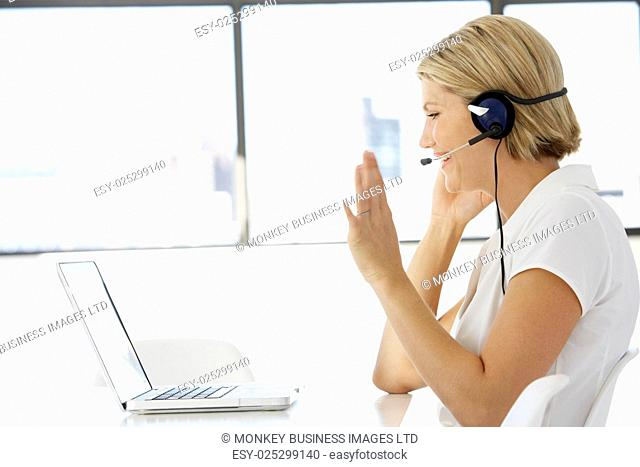 Businesswoman Sitting At Desk In Office Using Laptop Wearing Headset