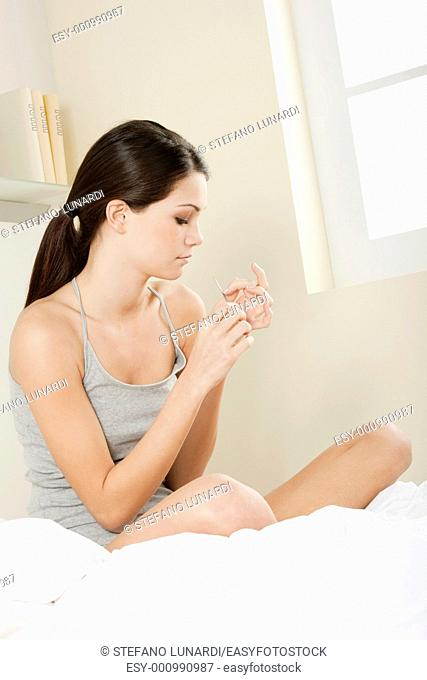 Teenage girl polishing fingernails with the nail file