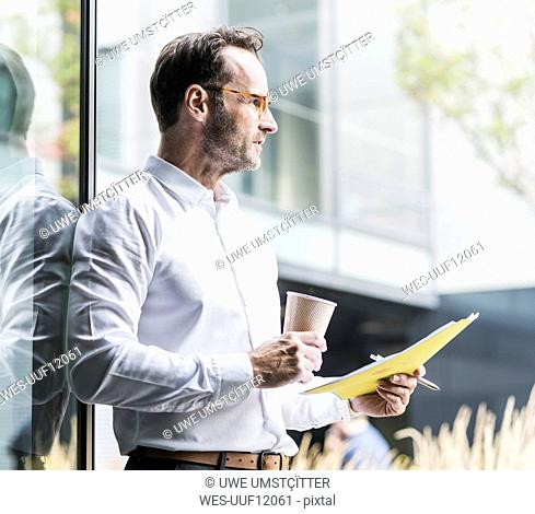Businessman with papers and coffee to go looking at distance