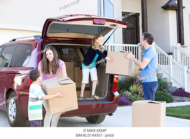 Caucasian family unpacking cardboard boxes from car