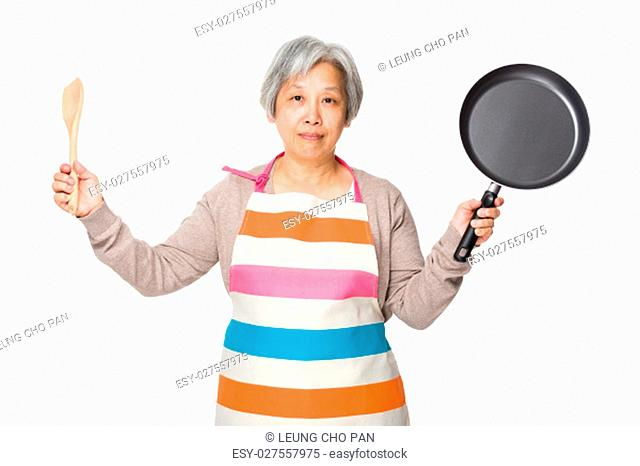 Old asian housewife holding up wooden ladle and frying pan
