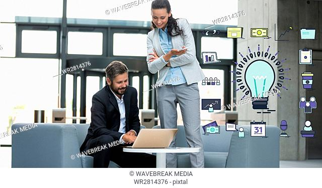 Business people using laptop by bulb sign in office