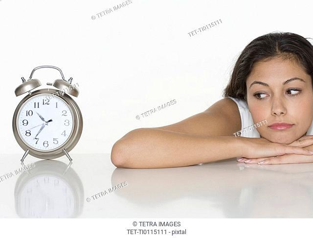 Woman looking at alarm clock