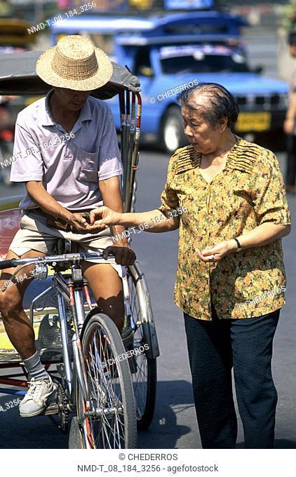 Mature woman paying a pedicab driver, Thailand