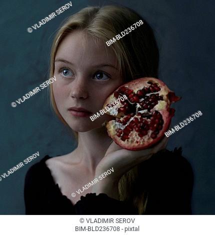 Caucasian girl holding pomegranate slice to cheek