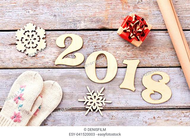 New Year 2018 handmade decoration on wood. Carved wooden number 2018, handmade wooden snowflakes, little gift box, craft paper and pair of mittens