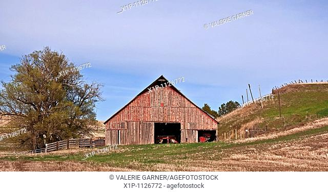 This rural photo is an image of an old, classic style red barn located in Eastern Washington state near Colfax in Whitman County with beautiful rolling hills