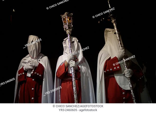 Hooded penitents holding a candle and a staff during an Easter Holy Week procession in Trujillo, Extremadura, Spain