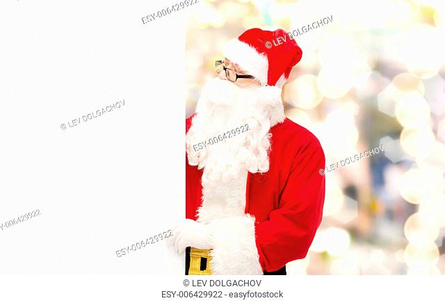 christmas, holidays, advertisement and people concept - man in costume of santa claus with white blank billboard over lights background