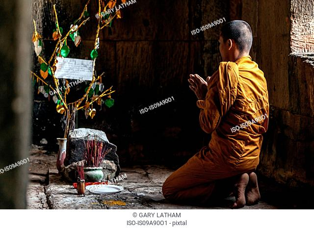 Young Buddhist monk praying inside temple in Angkor Wat, Siem Reap, Cambodia