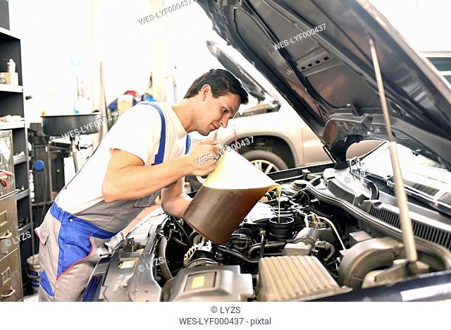 Car mechanic refilling engine oil