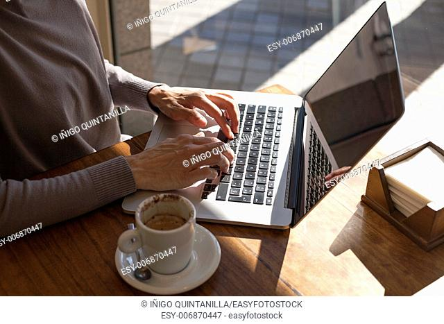 brunette mauve sweater woman typing keyboard pc laptop with white small cup cappuccino coffee on light brown wooden table cafe