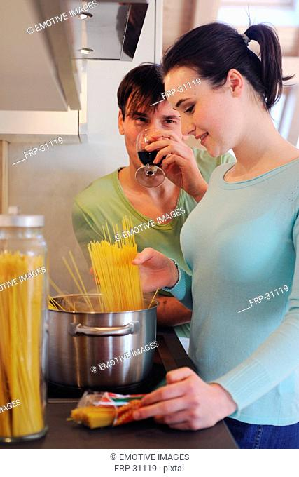 Young couple in kitchen cooking spaghetti and drinking red wine