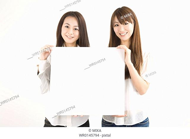 Two young women holding message board