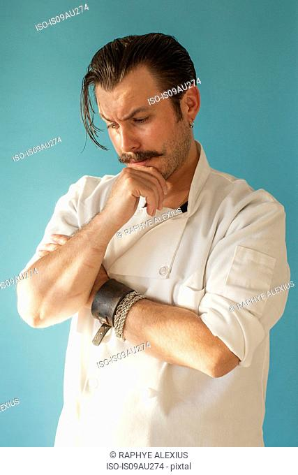 Studio portrait of mid adult male chef with hand on chin