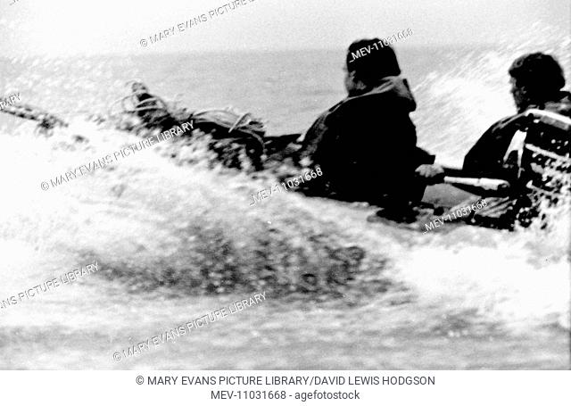 Two schoolboys in a motor-powered inflatable dinghy on the sea near Atlantic College (United World College of the Atlantic), St Donat's Castle, Llantwit Major