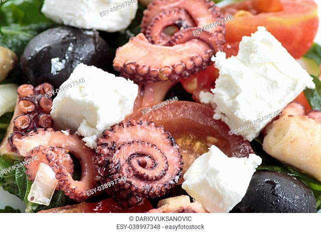 Octopus salad with rucola, olives and feta cheese close up