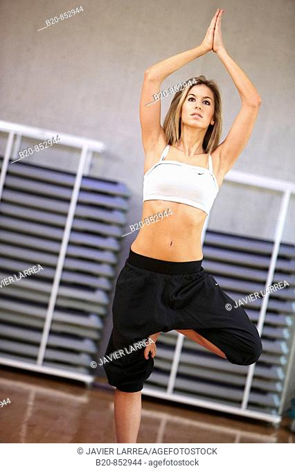 Young woman in gym doing yoga