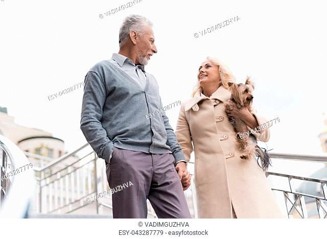 An elderly couple is walking. They go down the stairs. A woman has a dog in her arms. They smile and look at each other