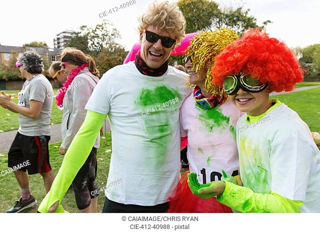 Portrait playful runners in wigs and holi powder at charity run in park