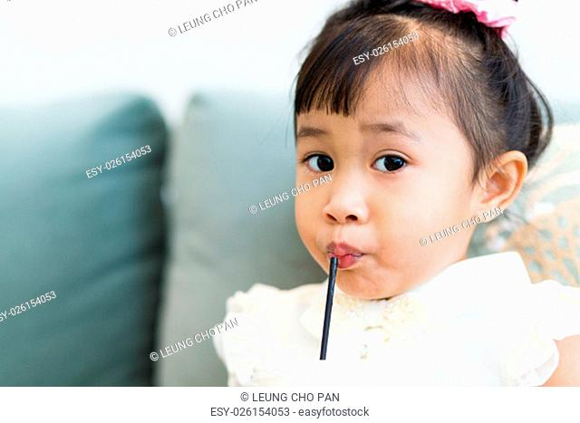 Asian little girl drinking with straw