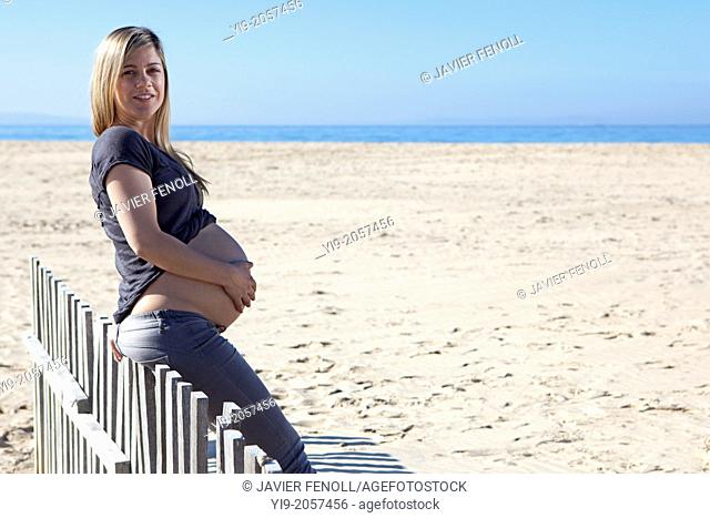 Pregnant woman sitting on wood fence