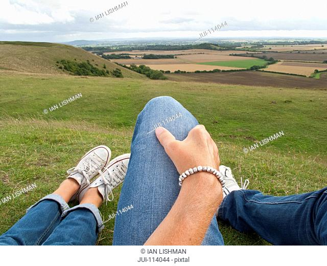 Woman with affectionate hand on leg of man relaxing as couple in countryside grass