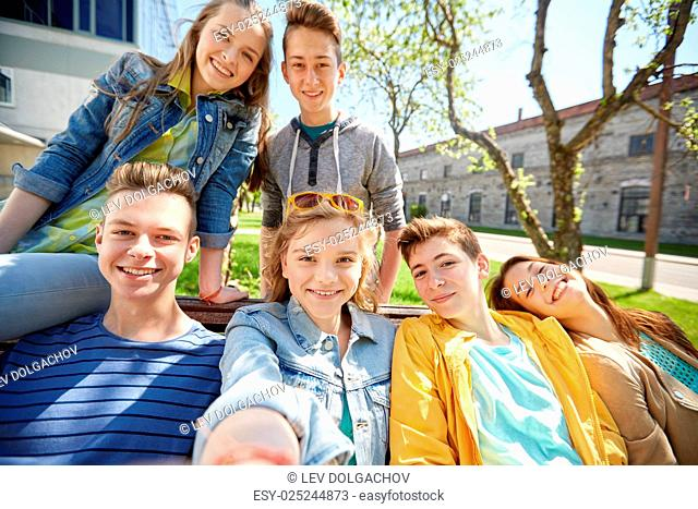 education, high school and people concept - group of happy teenage students or friends taking selfie