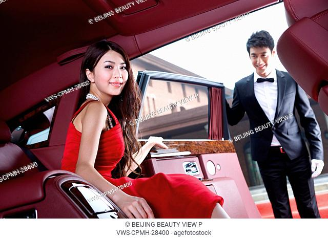 Young woman sitting in a luxury car