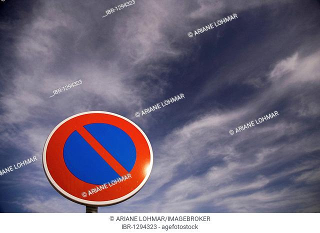 No stopping sign against a blue sky with clouds