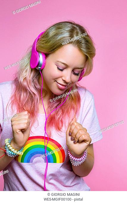 Portrait of dancing young woman listening to music with headphones in front of pink background