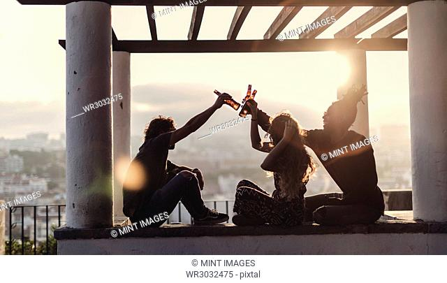 Silhouette of two men and a woman sitting outdoors under a pergola at sunset, holding aloft beer bottles, toasting