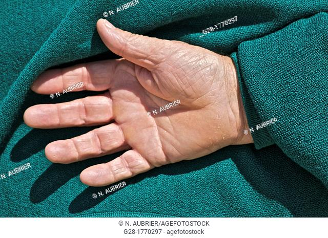 Senior man hand seen from the back, on green pull over