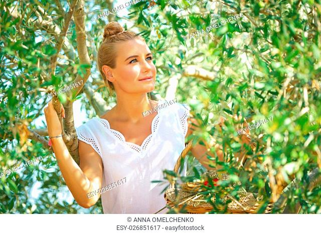 Portrait of a nice blond dreamy woman enjoying nature of a countryside, girl walking in the olive garden, harvesting time in autumn season