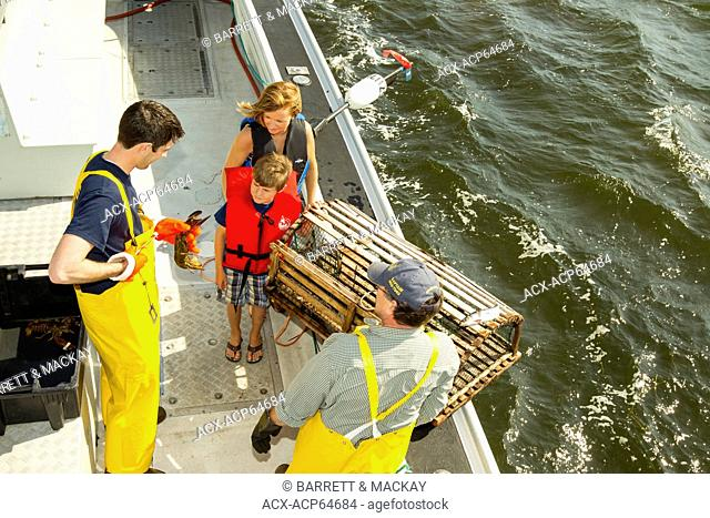 Young boy and mother talking to Lobster fishermen, Northport, Prince Edward Island, Canada