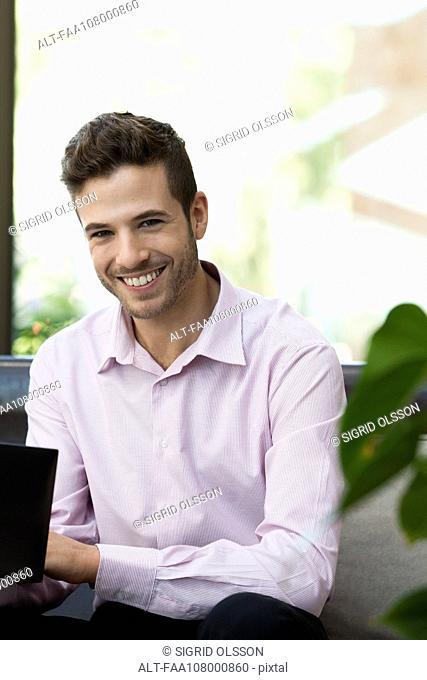 Businessman using laptop computer, portrait