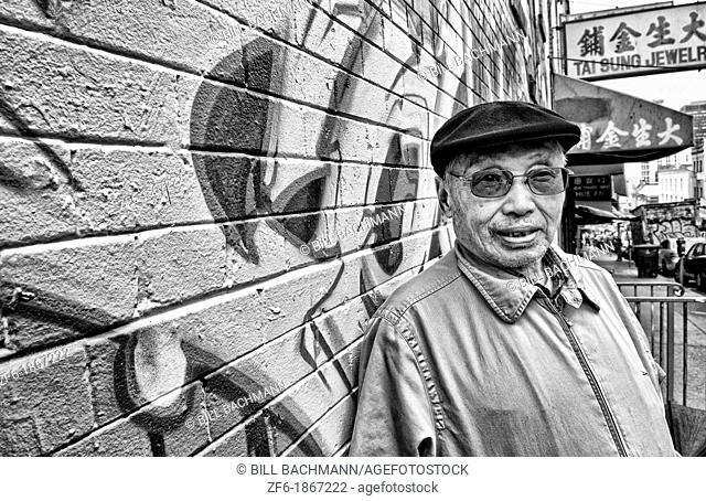 Old Chinese man with wall mural in Chinatown San Francisco California