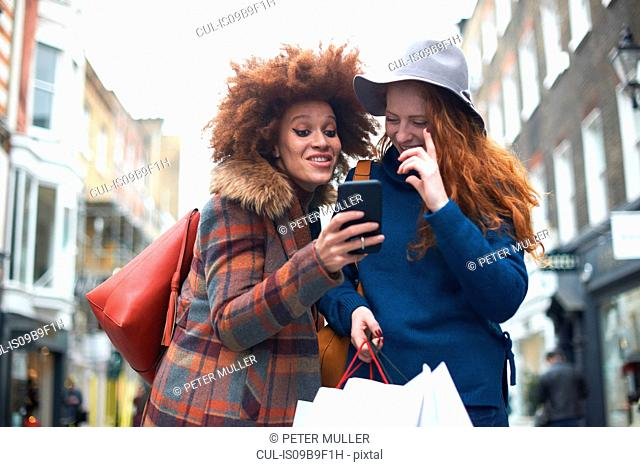 Two young women in street, looking at smartphone, laughing