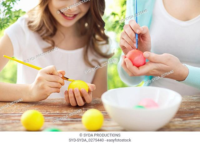 happy smiling girl and mother coloring easter eggs