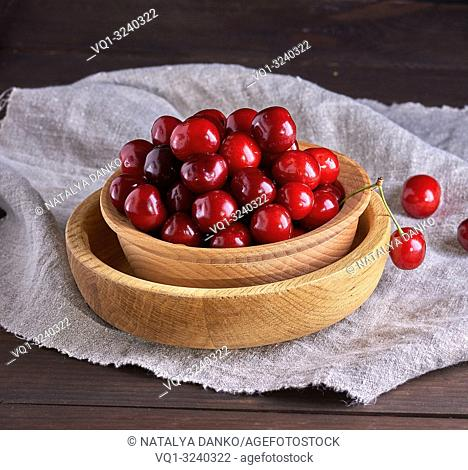 ripe red cherries in a brown wooden bowl on a brown table, close up