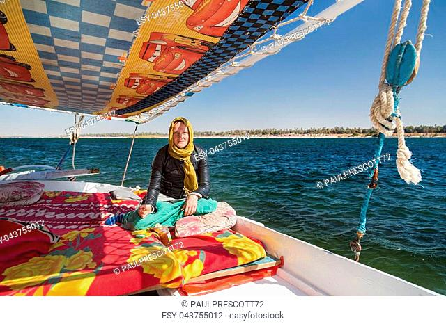 Female tourist eating snack during felucca trip on the Nile