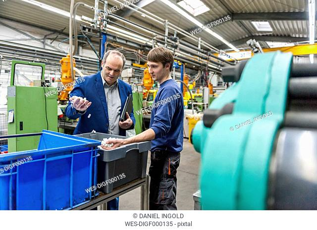 Manager and worker examining products in plastcs factory