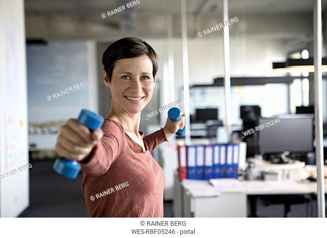 Smiling businesswoman in office exercising with dumbbells